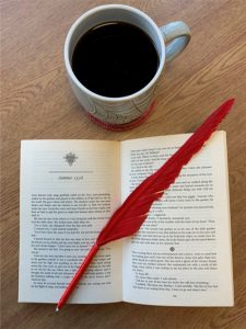 Coffee cup over open novel with red feather quill